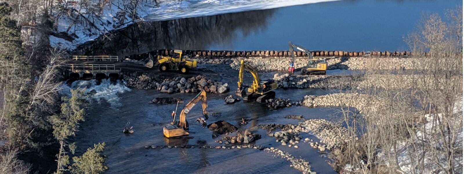 construction trucks dredging a river